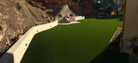 The Completed Atherton Artificial Grass Project showing beautiful artificial grass and the retaining wall with a built in drain.
